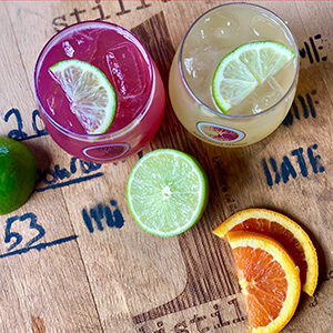 two cocktails on wood background with fruit