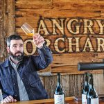 Ryan Burke looking at cider in a glass at Angry Orchard