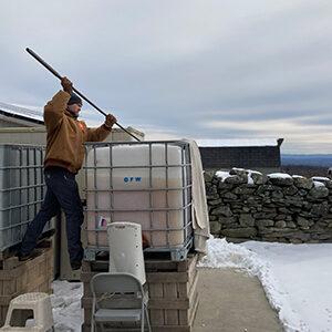 man in winter making ice cider
