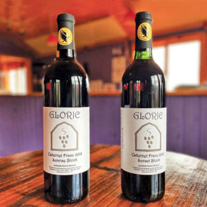 two bottles of Glorie Cab Franc side-by-side on wood table