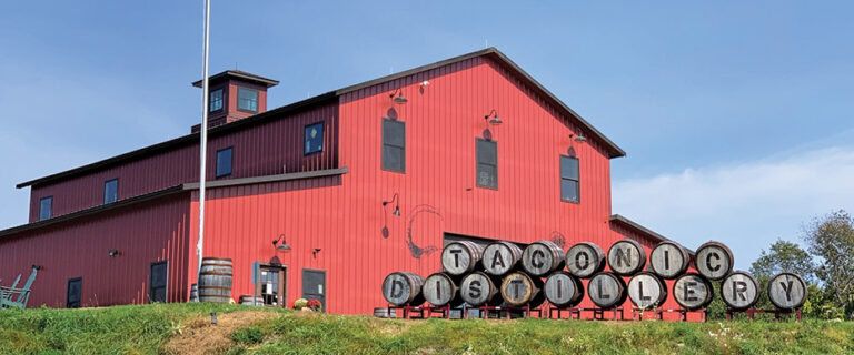 red barn with barrels in front