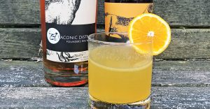 Taconic Sunrise cocktail with bottle of Taconic Distillery Rye Whiskey