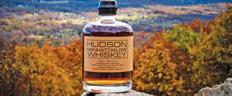 Bottle of Hudson Manhattan Rye Whiskey with colorful autumnal landscape background