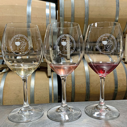 three glasses of wine in front of barrels