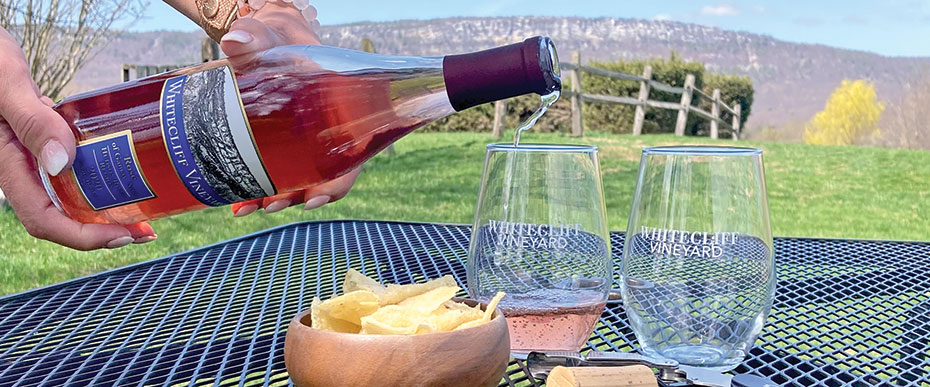 hand holding bottle of rose pouring wine into glass