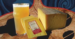 A glass of beer with two blocks of Hudson Valley cheese