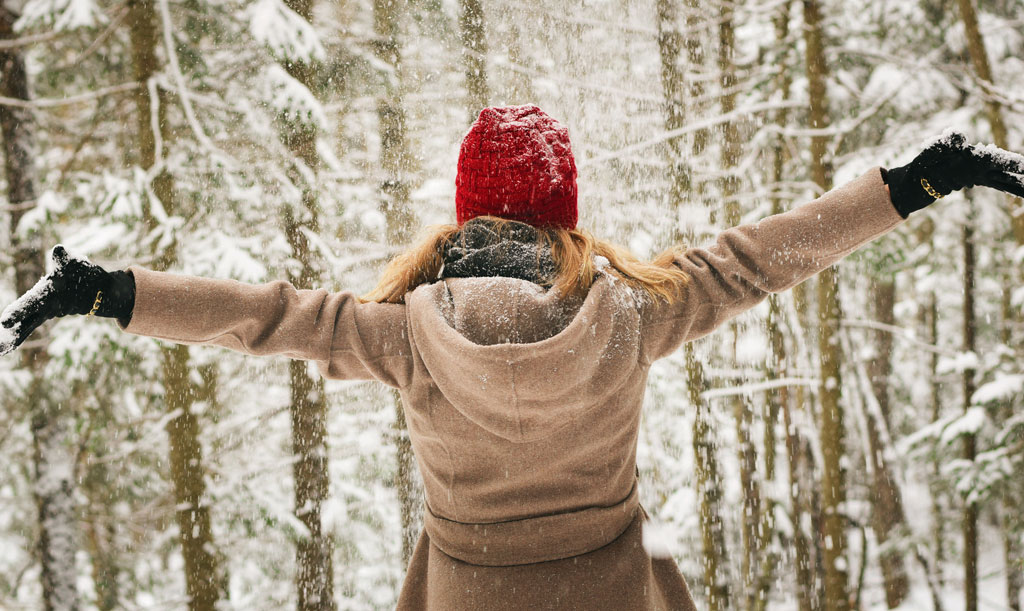 Girl standing backwards with hands in air facing a snow covered forest