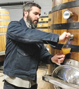 Ryan Burke pouring glass of cider from barrel, at Angry Orchard.