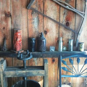 photo of the wood paneled wall, and shelf with vintage items, and small fruit press, at Bashakill Vineyards.