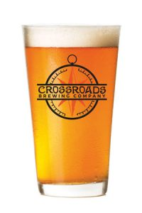 photo of full beer glass, with Crossroads Brewing Company logo