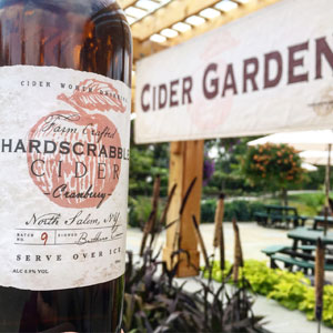 Closeup photo of a bottle from Hardscrabble Cider, with Cider Garden sign in background.