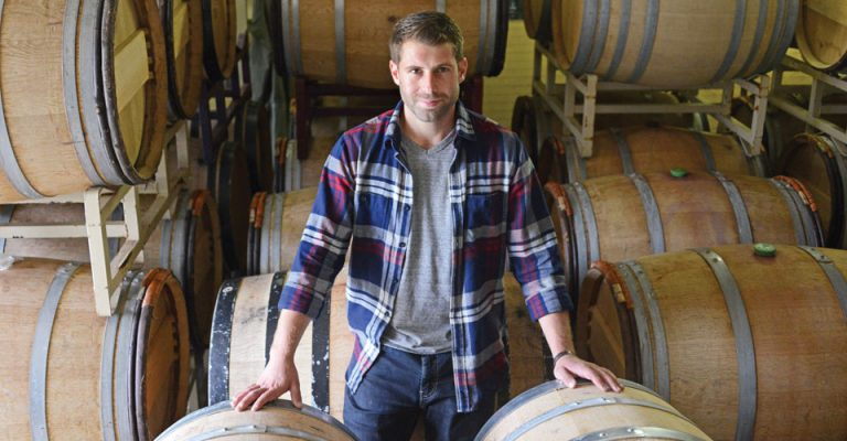 view of Jonathan Lander, assistant winemaker at Robibero Family Vineyards, standing by barrels