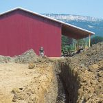 Photo of red building and trench-in-progress, at Whitecliff Vineyard, with Shawangunk mountains in the background.