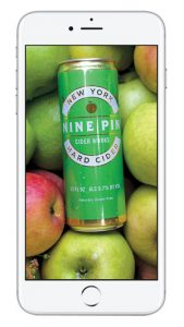 photo of white iPhone, with image of can of Nine Pin Hard Cider, and apples