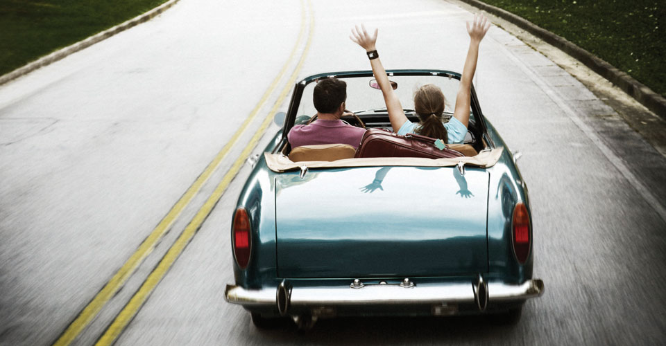photo of couple in a convertible car, driving down the road