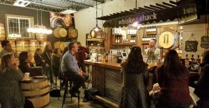 Photo of Whiskey Shack interior, with people listening to bartender