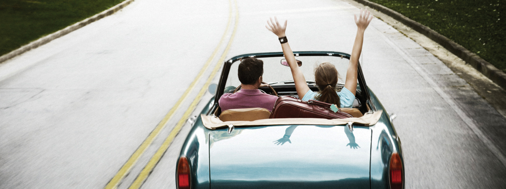 rear view of couple in car, with hands up, driving down a road.