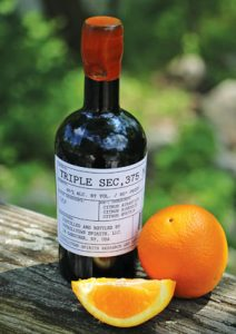 photo of Tuthill Town Distillery bottle of Triple Sec, with an orange and orange slice