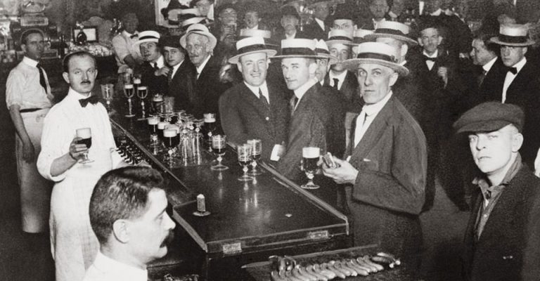 Vintage black & white photo of the interior of a crowded bar moments before midnight, June 30, 1919, when wartime prohibition went into effect, in New York City.