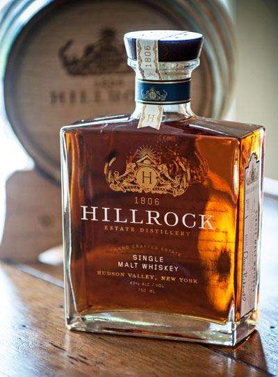 View of bottle of Single Malt Whiskey, from Hillrock Estate Distillery, with Hillrock cask in background.