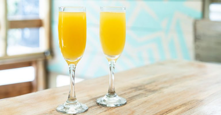 photo of two glasses of mimosas on tabletop.