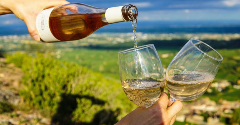 Photo of white wine being poured into two glasses, held by one hand.