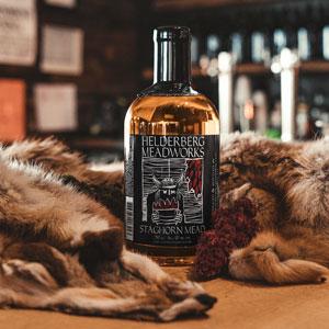 bottle of Helderberg Meadworks mead on wood table with fur pelts