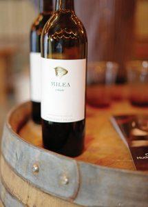 bottles of Milea Estate red wine on a wooden barrel