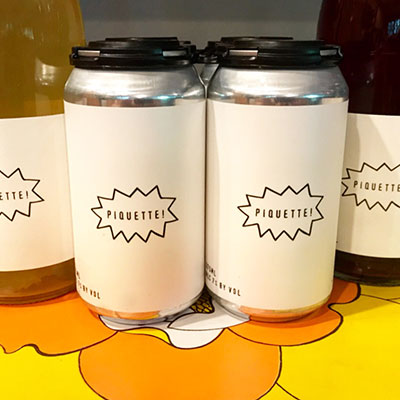 cans of piquette wine from Wild Arc Farms on a bright yellow and orange flowered tablecloth