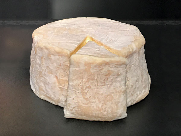 Large round of Gatekeeper cheese with a slice removed, on gray background.