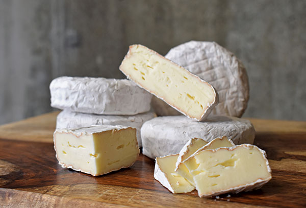 Stacks of Hartwell cheese in rounds and slices on wood tabletop.