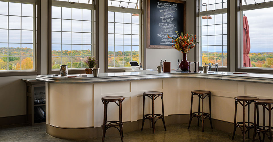 Milea tasting room interior showing windows, bar and stools.