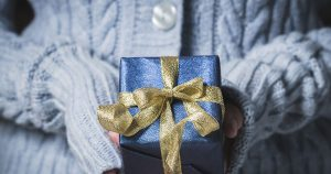 girl in blue sweater holding blue gift wrapped package with gold ribbon