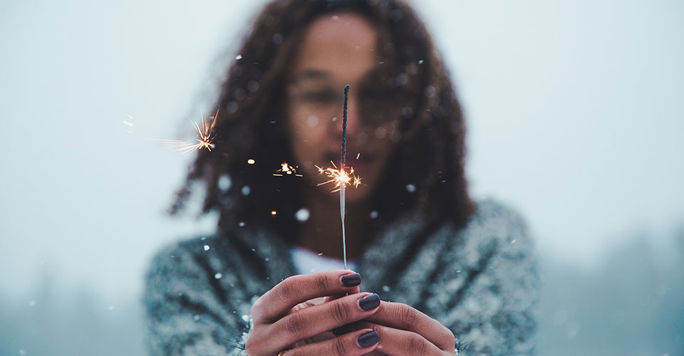 girl holding sparkler with soft blur background