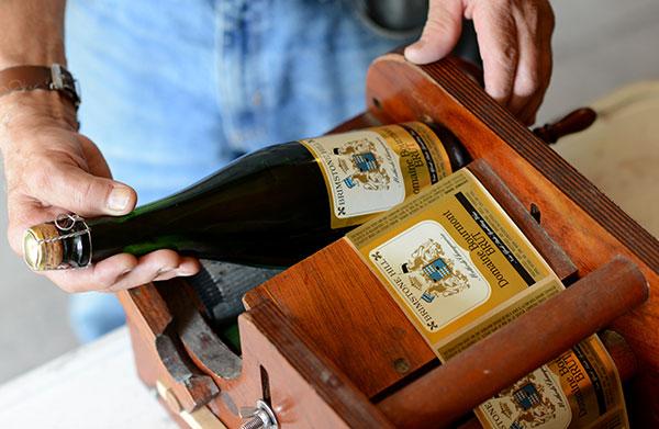 man putting gold label on bottle of sparkling wine using vintage wooden label machine