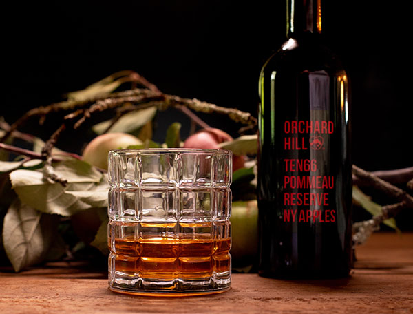glass of brown liquor with bottle  and apple branches on table