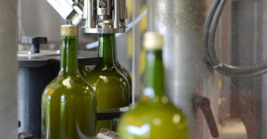 bottling line showing cap being place on a green bottle