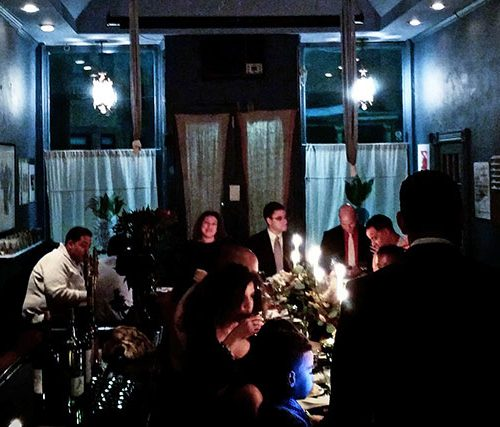 people eating at a long table inside a dark restaurant