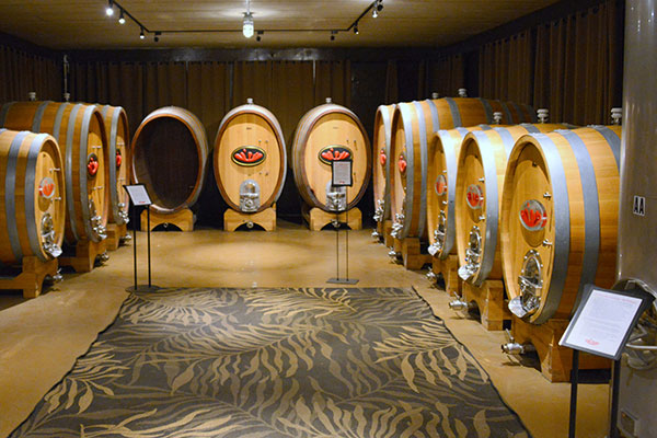 large wine barrels in a room with brown carpet
