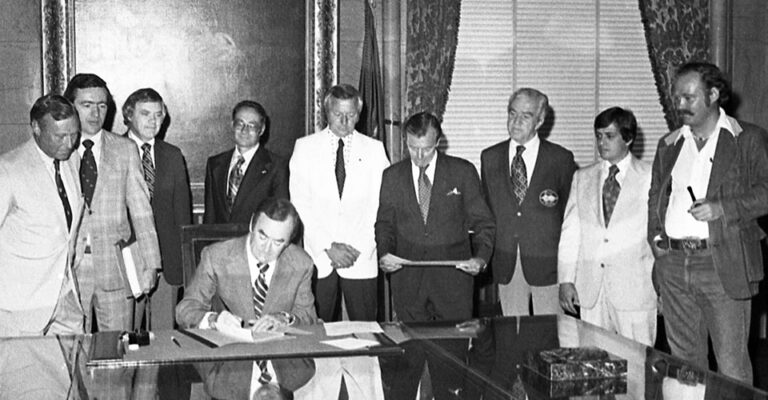 b/w photo of Gov Hugh carey signs document with group of men standing behind