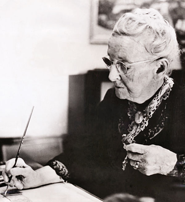 Grandma Moses with paintbrush working at a desk