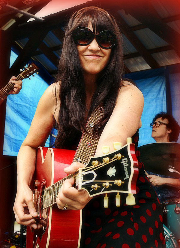 woman with sunglasses playing guitar