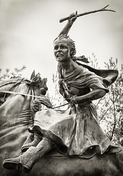 large statue of girl riding horse with hand raised