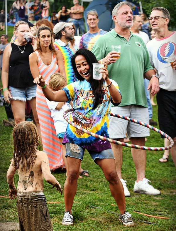 Woman in tie dye shirt with hula hoop in front of muddy child