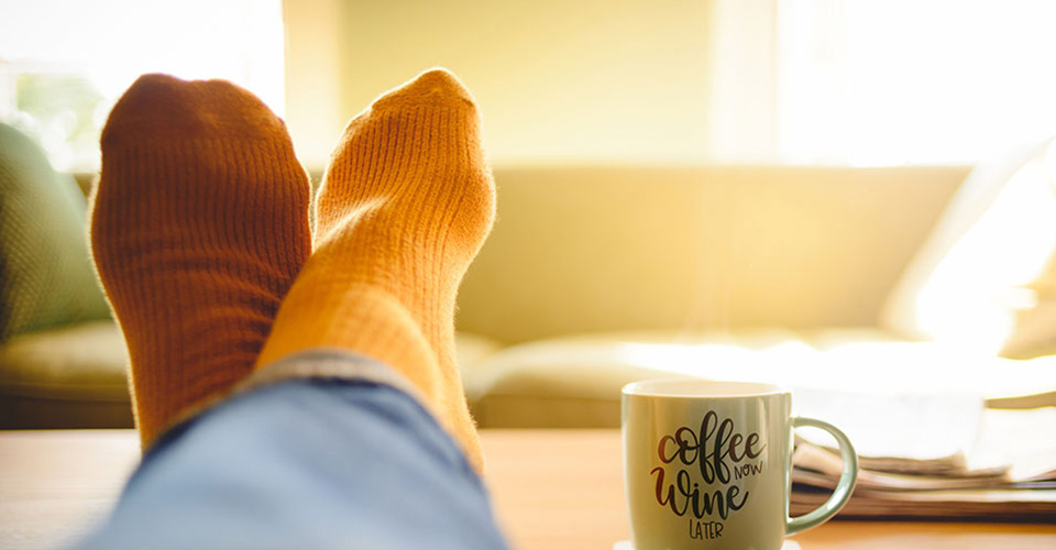 crossed feet up on a table with coffee cup