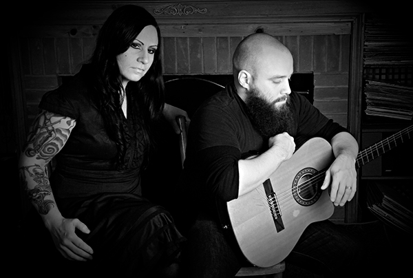 moody b/w photo of tatooed woman and man with guitar
