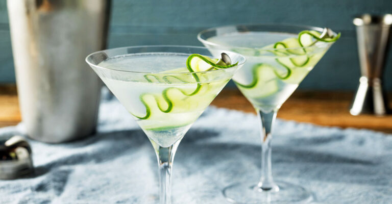 two sake martini glasses with cucumber ribbon garnish on a blue napkin