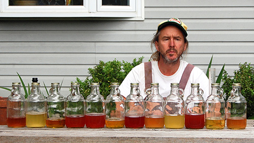 man looking at row of glass jugs with cider