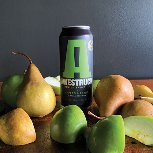 can of Awestruck cider with cut apples and pears in foreground
