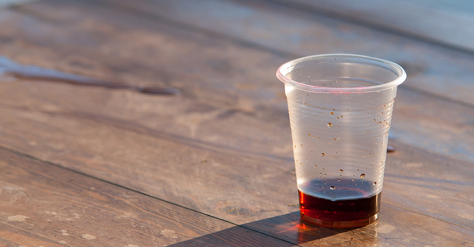 plastic cup with wine on wood table